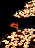 Mano di una mano anziana della donna che accende una candela durante il santo Immagini Stock Libere da Diritti