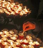 Mano di una mano anziana della donna che accende una candela durante il santo Fotografia Stock Libera da Diritti