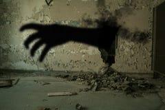 Mano diabolica che esce da foro in parete Fotografia Stock
