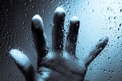Mano dietro la finestra bagnata fotografie stock libere da diritti