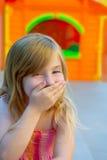 Mano divertida del gesto de la muchacha rubia del cabrito en boca Fotos de archivo libres de regalías