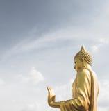 Mano dorata di Buddha 'sulla O k 'firmi (pace) con cielo blu e il clou fotografia stock libera da diritti