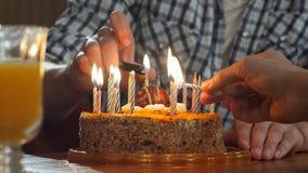 Mano dos que enciende velas en torta de cumpleaños Fotos de archivo
