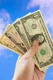 Mano e dollari sul fondo del cielo blu Fotografia Stock Libera da Diritti
