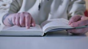 Mano e libro: leggendo un libro e tenuta delle vostre dita seguendo le linee La mano di una donna tiene un libro e muove le sue d stock footage