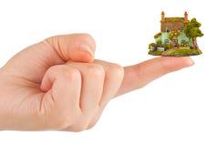 Mano e piccola casa Fotografie Stock