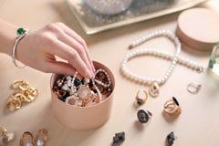 Mano e scatola femminili con gli accessori dei gioielli Fotografia Stock