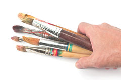Mano e spazzole usate dell'artista Immagini Stock