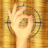 Mano ed obiettivo contro le monete di metallo giallo Fotografie Stock