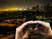 A mano el sostenerse y paisaje urbano binoculares en la noche Imagenes de archivo