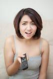 Mano emocionante de la mujer joven que sostiene la TV de observación teledirigida Foto de archivo libre de regalías