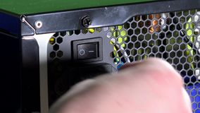 Mano en cable del enchufe de los guantes protectores a la prensa de la fuente de alimentación del ordenador en el botón almacen de metraje de vídeo