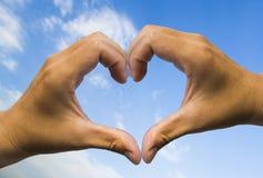Mano en cielo azul del amor de la forma del corazón Fotografía de archivo libre de regalías