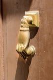 Mano en el golpeador de puerta de bronce Fotos de archivo libres de regalías