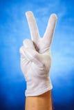Mano en el guante blanco que muestra la muestra de la victoria Imagenes de archivo