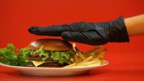 Mano en el guante que pone el bollo en la hamburguesa, cocinero que prepara la comida, comprobando calidad metrajes