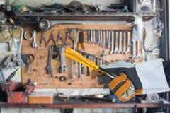Mano en el guante que sostiene el destornillador con las herramientas Imagen de archivo