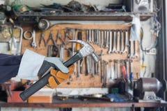 Mano en el guante que sostiene el martillo con el colgante de las herramientas Imagenes de archivo