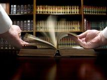 Mano en el libro de ley Imagen de archivo libre de regalías