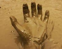 Mano en fondo del fango Imagen de archivo libre de regalías