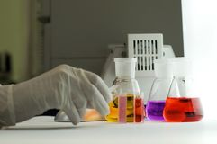Mano en guante con los frascos del laboratorio Fotos de archivo libres de regalías