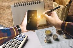 Mano en la camisa del inconformista que sostiene smartphone con la moneda de oro, calcul Fotografía de archivo