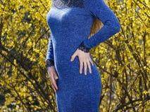 Mano en la cintura de una muchacha delgada en un vestido azul contra un fondo amarillo imagenes de archivo