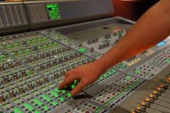 Mano en la consola de mezcla Foto de archivo