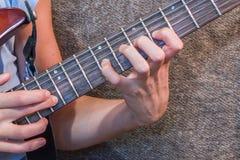 Mano en la guitarra eléctrica del cuello Foto de archivo