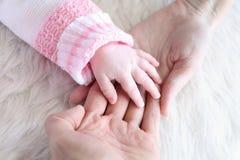 Mano en las manos de los padres, cierre del bebé para arriba Foto de archivo libre de regalías