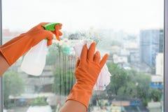 Mano en los guantes que limpian la ventana con el espray del trapo y de la despedregadora en ho foto de archivo