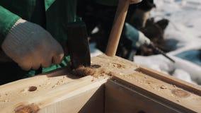 Mano en los guantes que martillan dos barras de madera para agujerear en el bloque de madera, invierno exterior metrajes