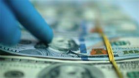 Mano en paquetes de mudanza del guante azul de dólares de EE. UU. en la superficie blanca Primer almacen de metraje de vídeo