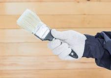 Mano en pinturas del cepillo de la tenencia del algodón del guante Imagen de archivo libre de regalías