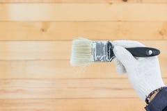 Mano en pinturas del cepillo de la tenencia del algodón del guante Imágenes de archivo libres de regalías