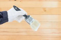 Mano en pinturas del cepillo de la tenencia del algodón del guante Fotos de archivo libres de regalías