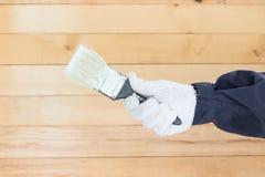 Mano en pinturas del cepillo de la tenencia del algodón del guante Foto de archivo libre de regalías