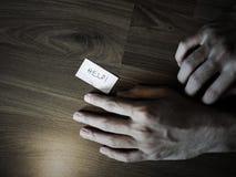 Mano en piso con la nota de la ayuda fotografía de archivo libre de regalías