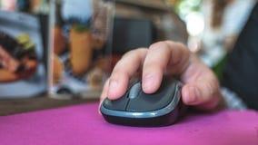 Mano en ratón del ordenador en cafetería foto de archivo libre de regalías