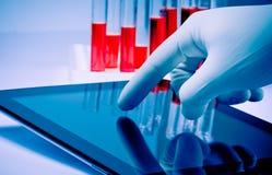 Mano en tableta digital moderna conmovedora del guante azul médico en laboratorio Foto de archivo