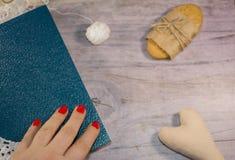 Mano en un libro azul Cordón blanco Fondo gris Foto de archivo libre de regalías