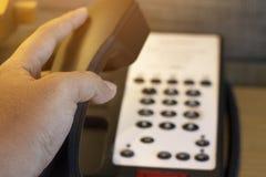 Mano encima del teléfono con el hotel imágenes de archivo libres de regalías