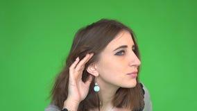 Mano entrometida joven sorprendida de la mujer a las noticias jugosas de la conversación del chisme del gesto del oído atento que metrajes