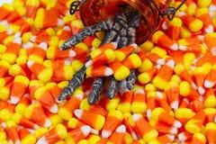 Mano esquelética asustadiza que viene hacia fuera tarro que da las pastillas de caramelo Foto de archivo libre de regalías