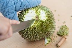 Mano facendo uso del coltello per sbucciare le coperture del durian che hanno molte spine Frutta stagionale tropicale, re di frut immagini stock