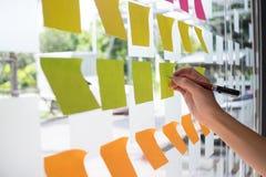 Mano facendo uso della nota appiccicosa di Post-it con 'brainstorming' sulla carta per appunti fotografie stock