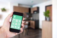 Mano facendo uso dello smartphone alla casa astuta app sul cellulare Fotografia Stock