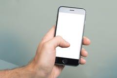 Mano facendo uso di Apple iPhone6 con lo schermo in bianco Immagine Stock Libera da Diritti
