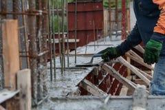 mano facendo uso di liscio la tirata del cemento con la cazzuola Fotografia Stock