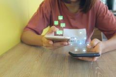 Mano feliz de la muchacha del inconformista que sostiene smartphone con el holograma o el icono foto de archivo